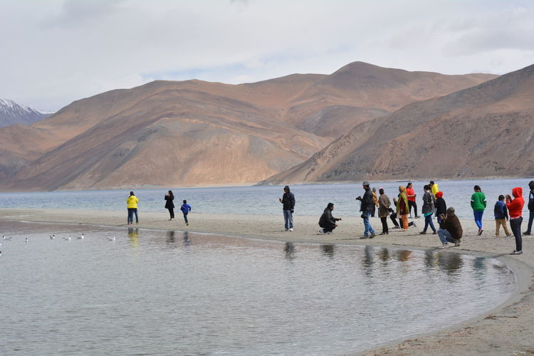 People At Shore Of Pangong Lake Against Mountains