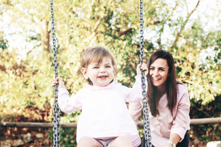 Mother pushing cute daughter swinging against trees in park