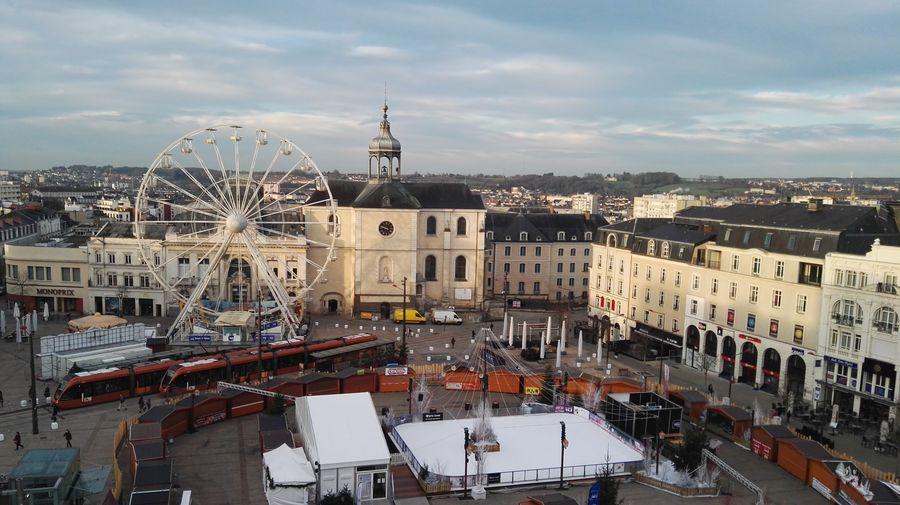 Ferris Wheel On Street By Buildings Against Sky