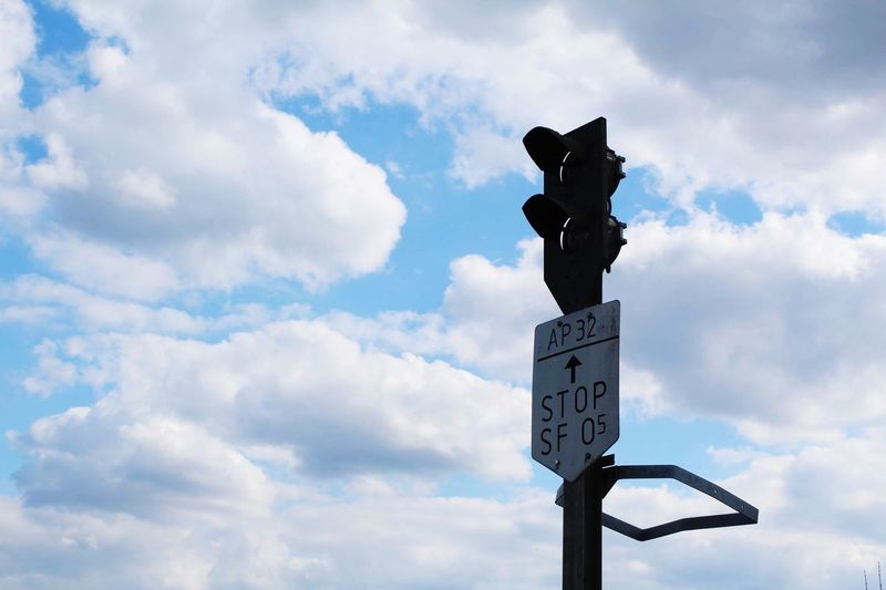 Low angle view of road signal with text against cloudy sky