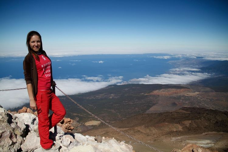 Full length portrait of smiling woman standing on mountain against sky at el teide national park