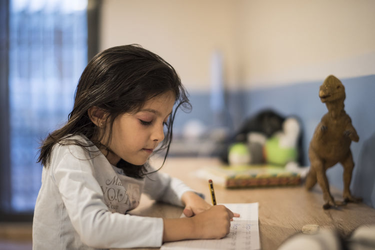 Girl writing on book at home