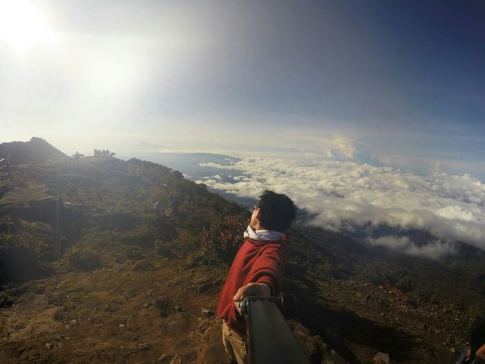 Man taking selfie while standing on mountain against cloudy sky