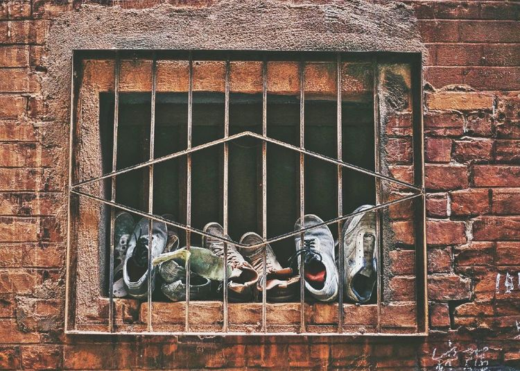 View of shoes in window in brick wall