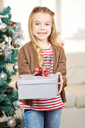 Portrait Of Smiling Girl Holding Gift During Christmas At Home