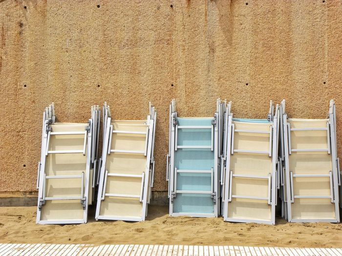 Beach Sand Deck Chair Deck Chairs In A Row Folded Up Bad Day At The Beach Summer Pastel Colors In A Row Stack Stacked Beige Tones Beige Beige And Blue Tan Colour Summer Day Odd One Out in Italy