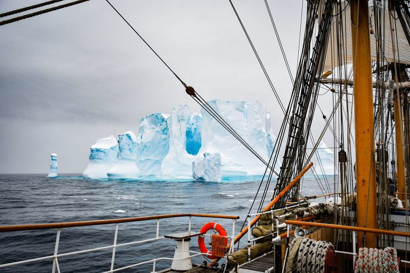 Tall ship by iceberg in sea against sky