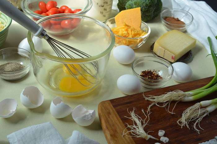 egg yolks, whisk in glass mixing bowl--whole unbroken eggs, cheddar cheese, Gruyere cheese, shredded Swiss cheese, black pepper, red pepper, nutmeg in small glass dishes, broccoli, Grape tomatoes in bowl in back, green onions on cutting board--ingredients for making Quiche Cheese Cooking At Home Egg Yolks Eggs Food Fresh Ingredients Kitchen Utensils Preparation  Quiche Still Life Whisk