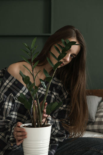 Portrait of young woman hiding behind potted plant
