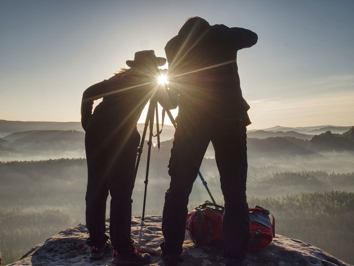 Two hikers take pictures and talk on top of mountain. photographers with photo gear relaxing on top