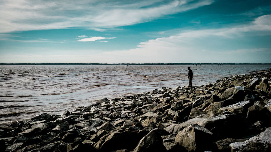 Man Standing On Rocks By Sea