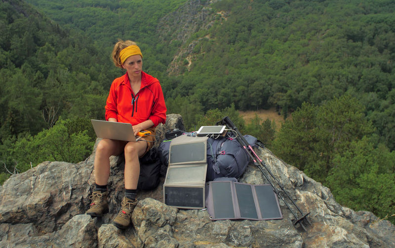 caucasian female hiker sitting on a rock while working on a laptop being charged by solar panels nearby, portable solar charing technology concept Backpacking Camping Charing Cross Freedom Hiking Nature Sitting Solar Panel Tablet Travel Trekking Woman Working Adult Adventure Battery Connection Day Female Front View Full Length Internet Laptop Leisure Activity Looking At Camera Mountain Nature Navigation One Person Outdoors People Portable Information Device Rock Rock - Object Sitting Solid Technology Tree Young Adult Young Women