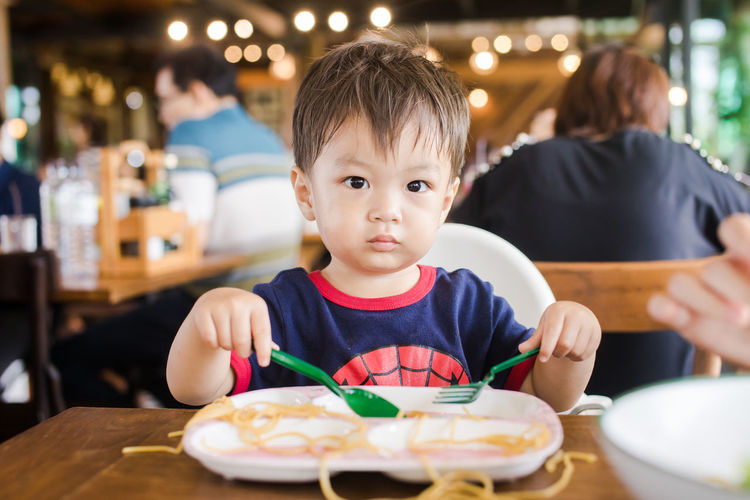 Cute baby boy having meal at restaurant