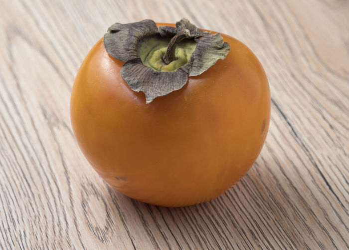 Whole ripe persimmon fruit on wooden background. Sweet, Orange, Fresh, Nutrition, Fruit, Diet, Persimmon, Delicious, Vegetarian, Food, Vitamin, Ripe, Asian, Healthy, Tropical, Ingredient, Juicy, Dessert, Tasty, Background, Raw, Nature, Natural, Chinese, Nutritious, Exotic, Eat, Edible, Color, Freshness, Food And Drink Food Healthy Eating Wellbeing Freshness Close-up Vegetable Wood - Material No People Single Object Fruit Persimmon Table Indoors  Orange Color Still Life Focus On Foreground Day Nature Wood Grain