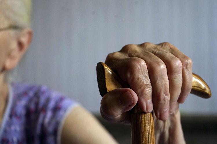 Close-up of senior woman holding walking cane