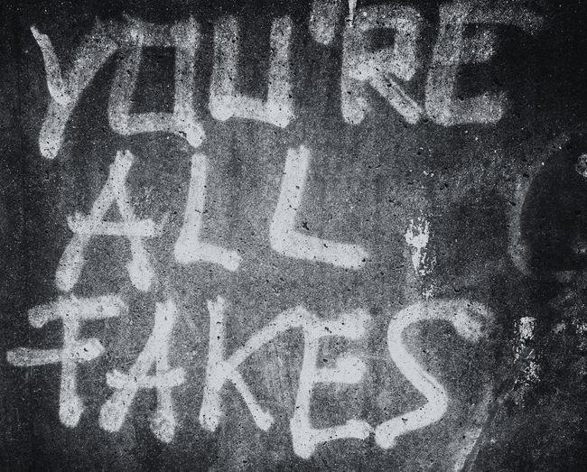 Graffiti on a concrete wall Graffiti Wall Write Architecture Black Blackandwhite Close-up Communication Day Fake Full Frame Graffiti & Streetart Graffiti Art Graffiti Wall No People Outdoors Text Texture You Are All Fakes