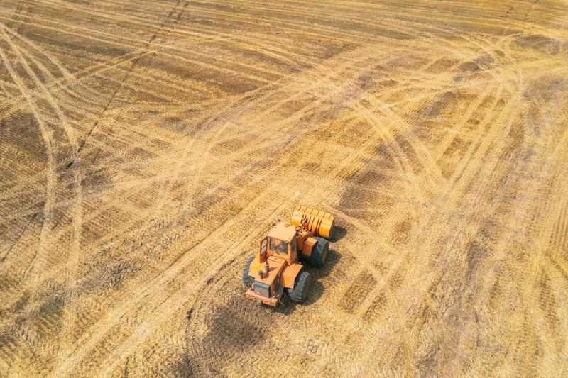 Orange tractor driving through the mown wheat field. farmers at work. agriculture harvesting season.
