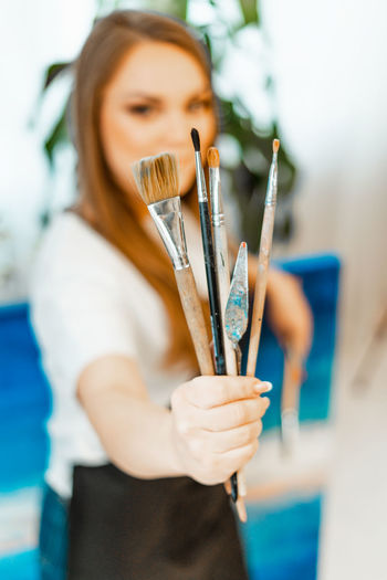 Portrait of woman holding paintbrush