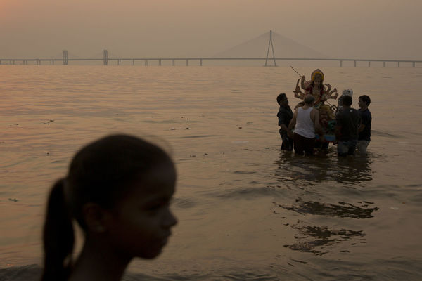 A young girl watches on as an idol of goddess Durga is carried into the arabian sea as a part of durgapuja celebrations in Mumbai, India. Durga Durgapuja Girl Godess Hindu Hinduism Sunset Water