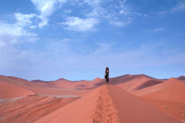 Woman standing on sand dune in desert against blue sky