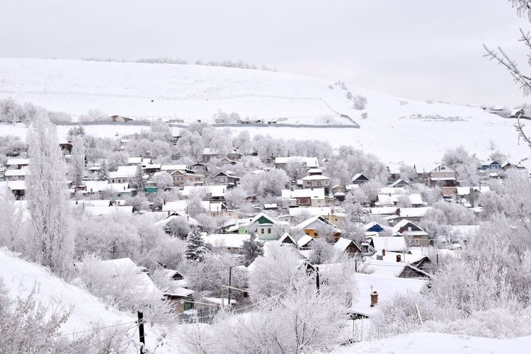 Aerial view of townscape by snow covered houses