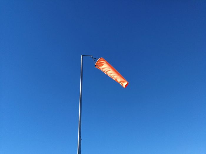 Low angle view of windsock flying against clear blue sky