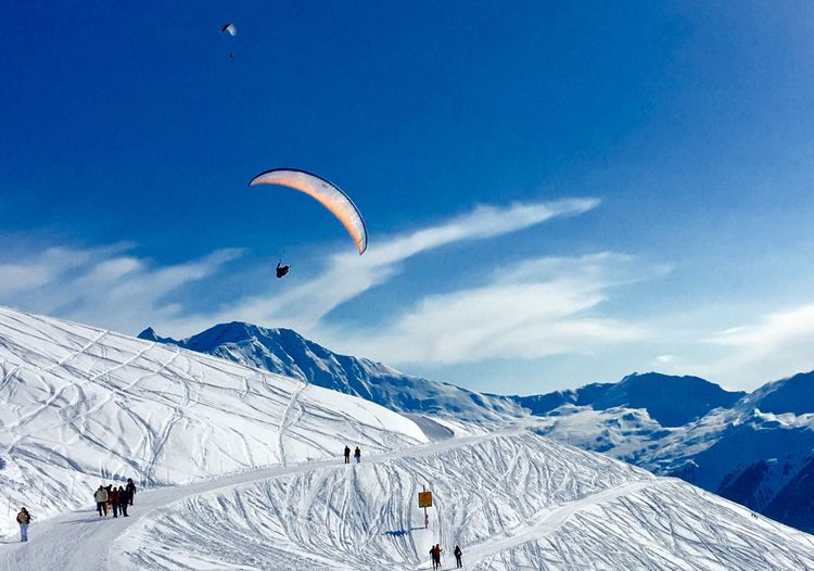 Person flying over snowcapped mountain against blue sky
