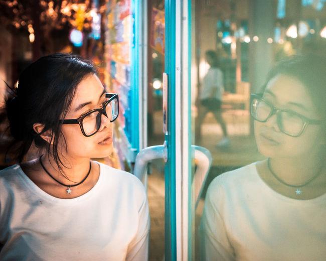 Woman wearing eyeglasses looking in window at night