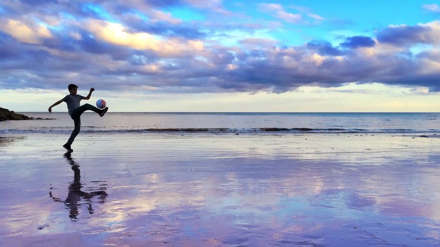 Teenage boy playing with ball at beach against dramatic sky