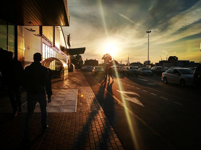 People on road in city at sunset
