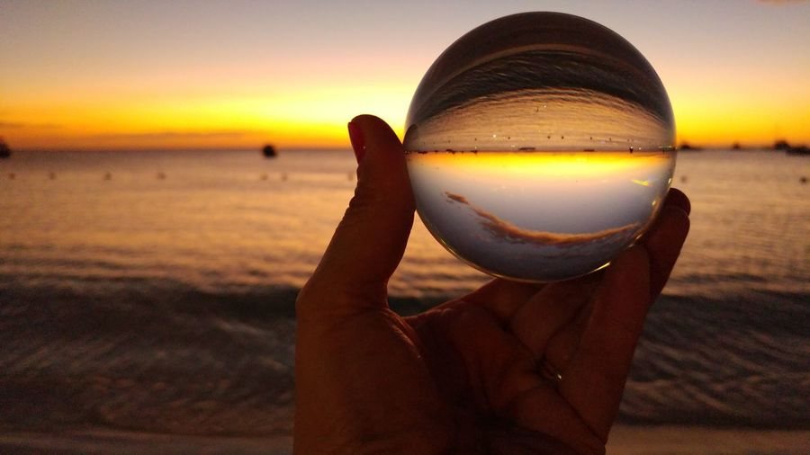 Close-up of hand holding crystal ball with sea reflection at sunset