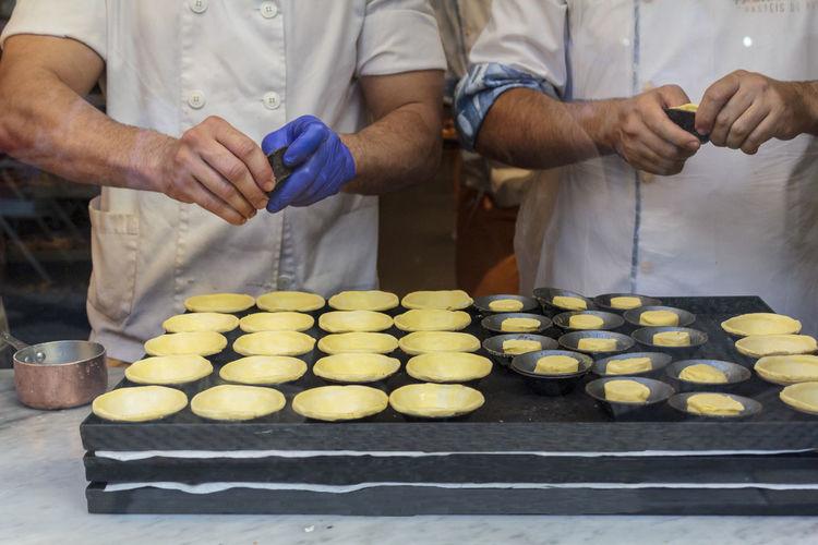 Confectioners making dough for the famous portuguese egg tart pastel de nata