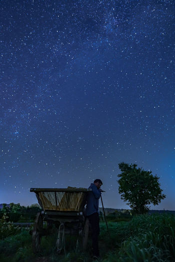 Man on field against sky at night