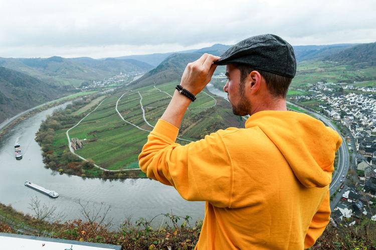 Man standing on mountain overlooking lake