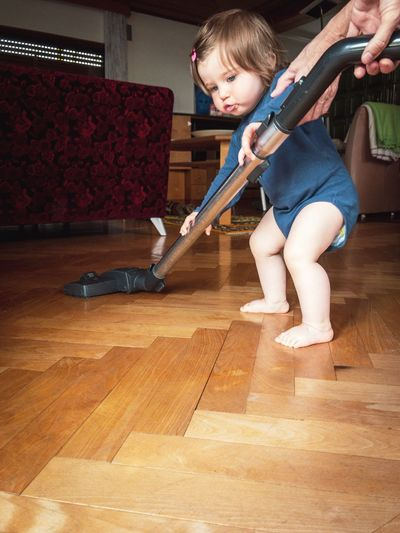 Cute girl standing on hardwood floor at home