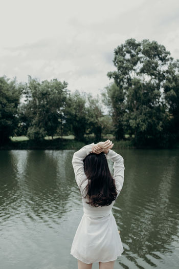 Rear view of woman standing by lake against sky