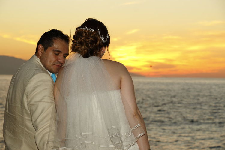 Newlywed Couple Sitting Against Sea During Sunset