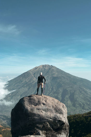 People standing on rock against mountain. mount merapi, indonesia
