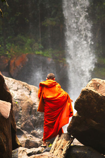 Rear view of monk standing on rock against waterfall