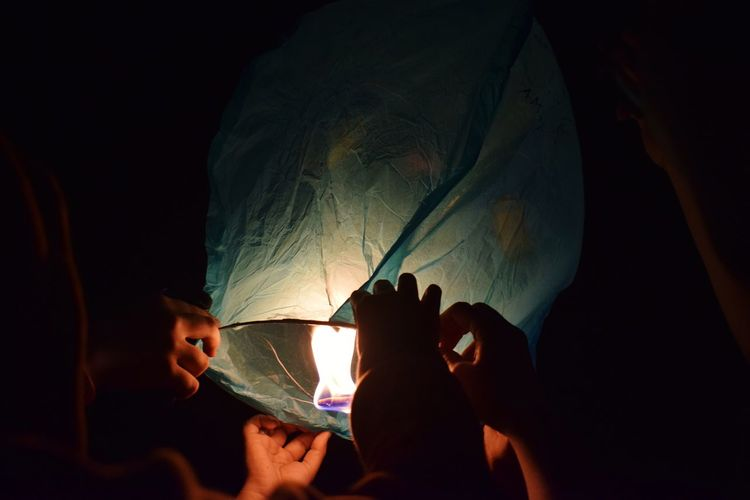 Cropped hands of friends holding lit paper lantern at night