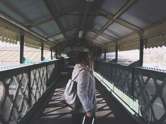 Young woman walking on covered bridge at railroad station