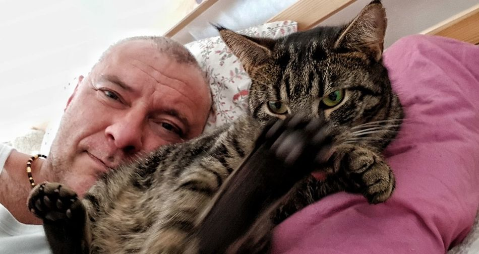 Portrait Of Man With Cat Lying On Bed