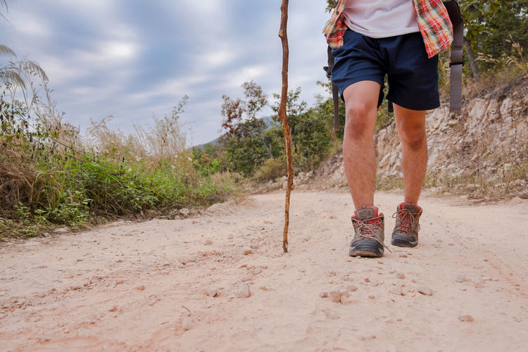 Low section of man walking with stick on dirt road