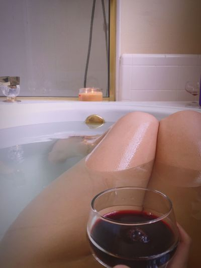 Low Section Of Woman Lying In Bathtub With Wine
