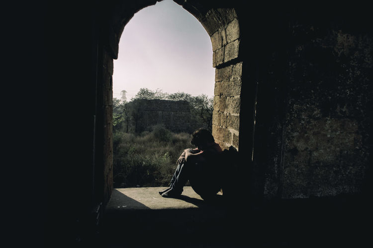Depressed man sitting at arch window of historic building