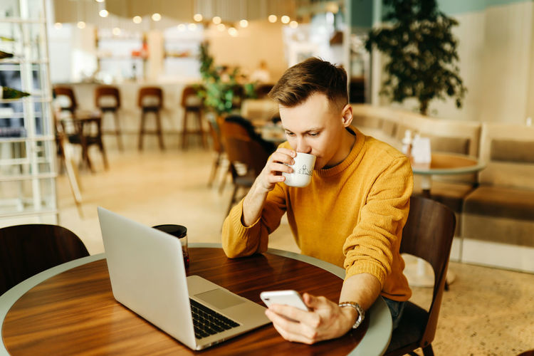 Young woman using laptop in coffee cup