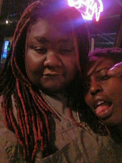 Illuminated Looking At Camera Outdoors Crowd Confidence  Awkwardly Awesome Close-up Dreadlocs Lesbian Melanin Darksin Lips Beautiful Skin Facial Expression Beautiful Woman Photobombed Nightlife Friendship Togetherness Adults Only PhotobombersAttack Drunk Friends Fun Only Women People