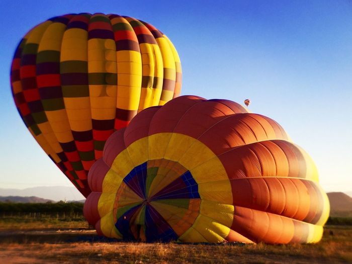Hot air balloons on landscape against clear blue sky