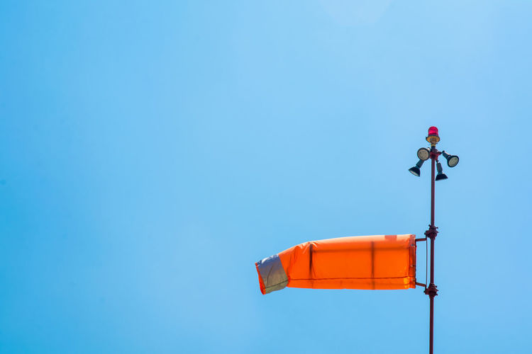 Low angle view of orange windsock waving against clear blue sky