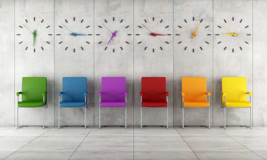 Colorful empty chairs arranged against wall with clocks